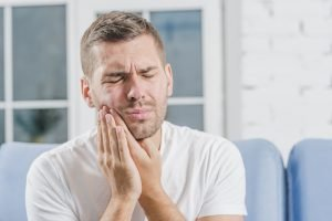 male holding side of mouth in pain experiencing a dental emergency image
