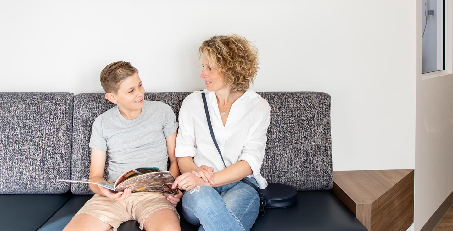 Mother and young boy in reception at Whites Dental Care image